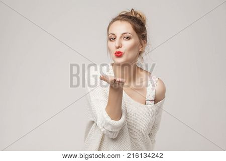 Romantic woman send air kiss at camera. Studio shot isolated on gray background stock photo