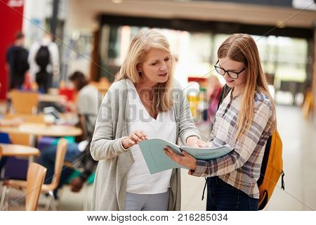 Teacher Talks To Student In Communal Area Of College Campus stock photo
