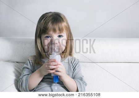 Little girl making inhalation with nebulizer at home. child asthma inhaler inhalation nebulizer steam sick cough concept Horizontal stock photo