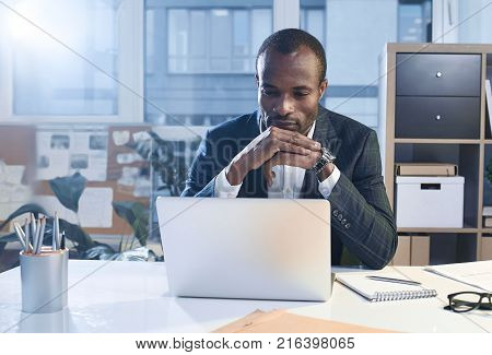 Business project. Portrait of serious young elegant african man is sitting at table while putting elbow on desk and touching his chin. He is looking at screen of modern laptop thoughtfully. Copy space