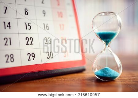 Hour glass and calendar concept for time slipping away for important appointment date, schedule and