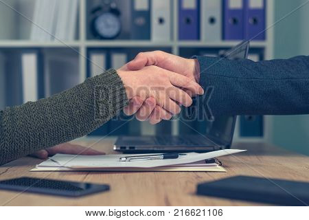 Man and woman shake hands over business agreement. Start up business female entrepreneur making handshake deal with large corporate company for selling small business. stock photo