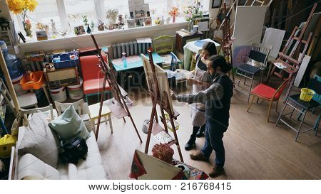 Skilled artist man teaching young girl painting on easel at art school studio - creativity, education and art people concept stock photo