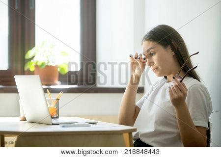 Young female worker with tired eyes holding glasses. Woman feeling discomfort from long wearing eyeglasses behind laptop at workplace. Eyesight strain from computer work concept stock photo