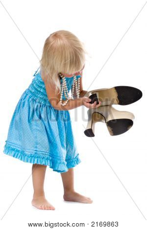 funny little blonde girl in blue dress and pearl necklace with pair of big high-heeled shoes in hand isolated on white stock photo