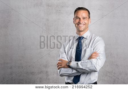 Happy businessman looking at camera on grey background with copy space. Handsome young business man