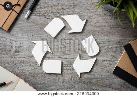 Top view of recycle sign on vintage wooden table with office equipment. High angle view of recycle l