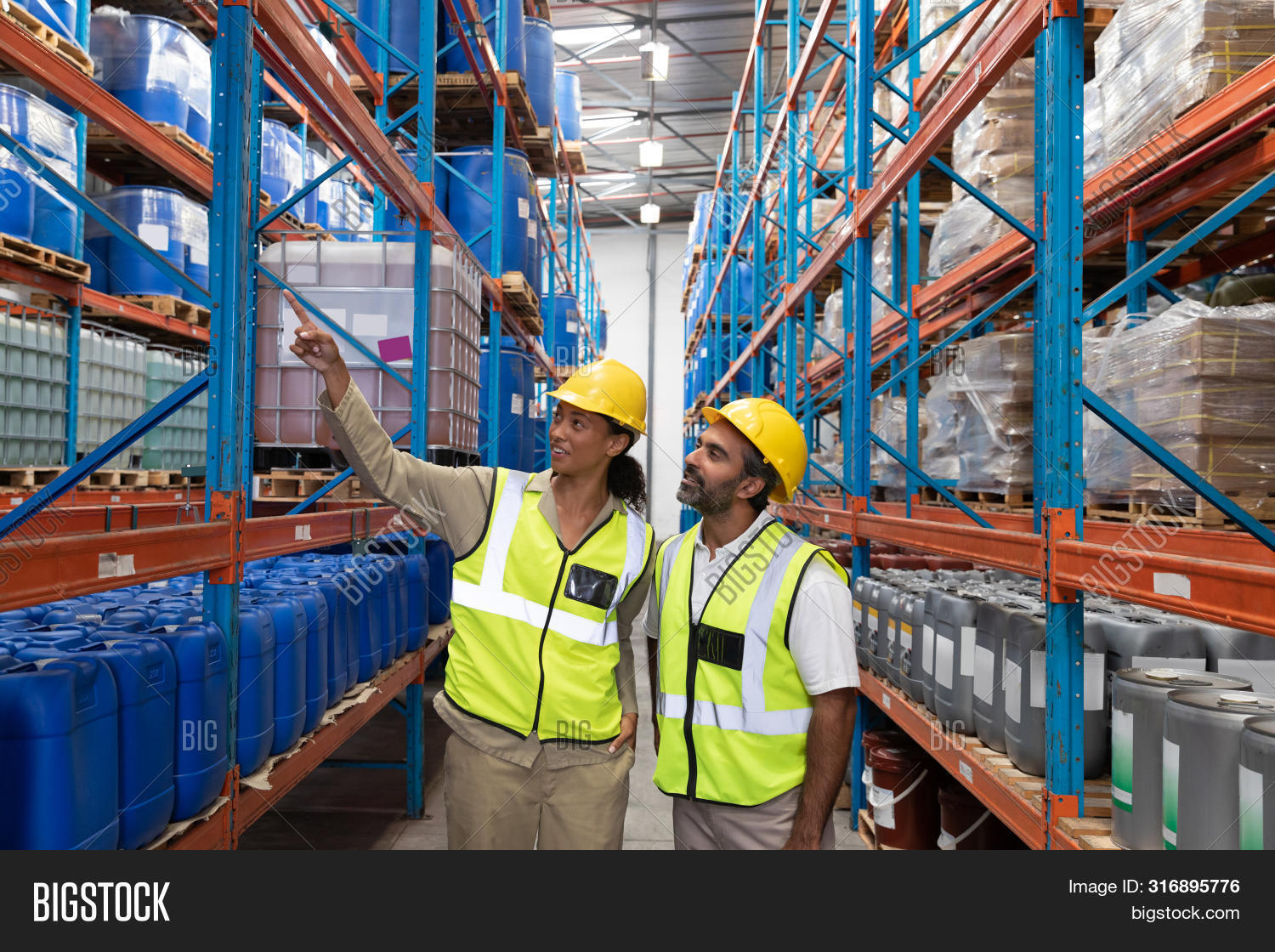 Front view of female worker showing something to male worker in warehouse. This is a freight transpo