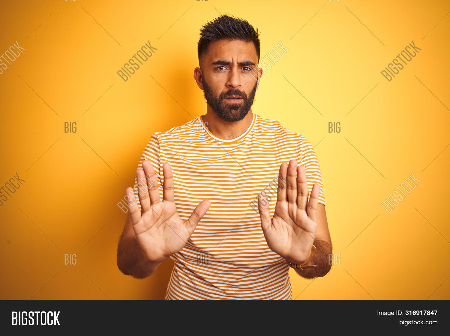 Young indian man wearing t-shirt standing over isolated yellow background Moving away hands palms sh