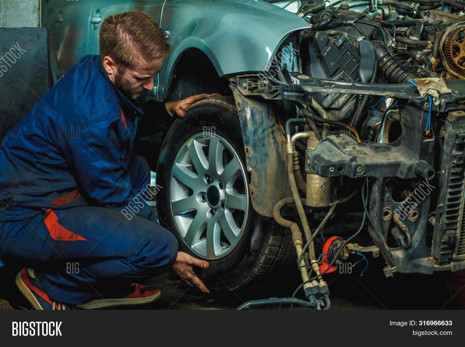 adult,auto,automobile,automotive,background,car,caucasian,change,changing,equipment,fixing,full,garage,holding,maintenance,male,man,mechanic,one,people,person,portrait,repair,rubber,service,shop,technician,tire,tool,transport,transportation,tyre,vehicle,wheel,work,worker,workshop,young