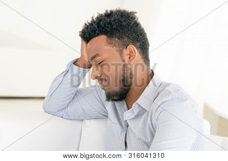 African Man suffering from headache migraine pain at home on sofa. Male holds head with hand. Concept of health. stock photo