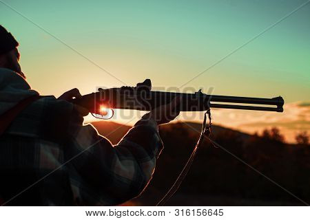 Hunter man. Barrel of a gun. Rifle Hunter Silhouetted in Beautiful Sunset. Hunter with Powerful Rifle with Scope Spotting Animals. Copy space for text stock photo