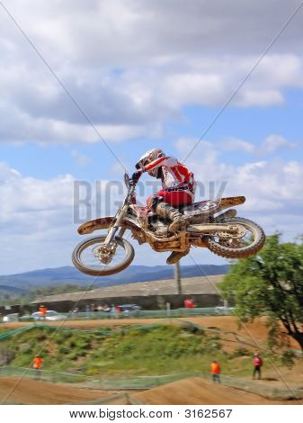 Motorcycle rider caught in mid-air making an acrobacy. stock photo