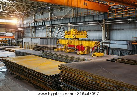 Overhead crane with electromagnetic beam grippers lifting steel sheets. stock photo