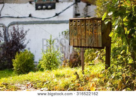 The rusty old mailboxes on the autumn nature. Abandoned iron mailboxes with house numbers. stock photo