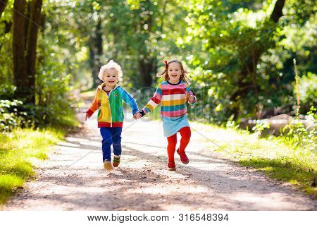 Kids picking ripe red apples from tree in country farm on sunny autumn day. Boy and girl pick fruit in apple orchard. Kid with basket. Child having fun during harvest time. Children play outdoor. stock photo