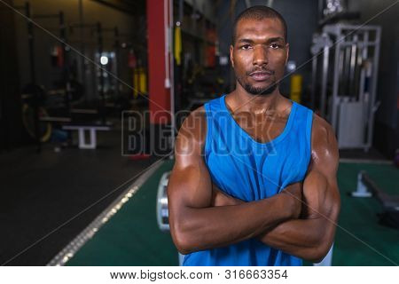 Portrait of male African-american athletic standing with arms crossed in fitness center. Bright modern gym with fit healthy people working out and training stock photo