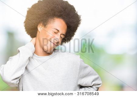 Young african american man with afro hair wearing sporty sweatshirt Suffering of neck ache injury, touching neck with hand, muscular pain stock photo