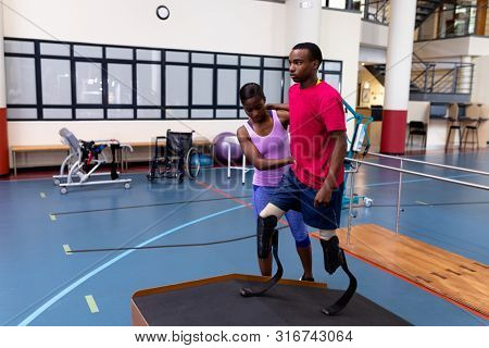 Front view of African-american Female physiotherapist helping disabled African-american man walk with prosthetic leg on ramp in sports center. Sports Rehab Centre with physiotherapists and patients stock photo