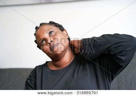 African woman with glasses suffering from neck pain on couch at home. A woman's sense of fatigue, exhausted, stressed. A girl massages her painful neck with her hands. The concept of health. stock photo