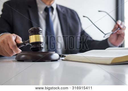 Judge gavel with Justice lawyers, Businessman in suit or lawyer working on a documents in courtroom. Legal law, advice and justice concept. stock photo