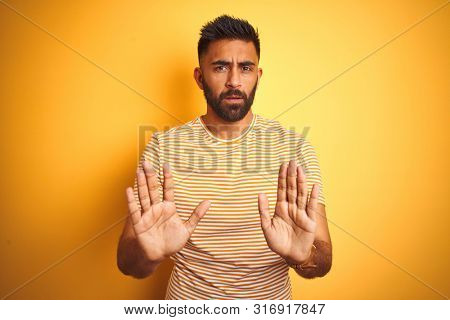 Young indian man wearing t-shirt standing over isolated yellow background Moving away hands palms showing refusal and denial with afraid and disgusting expression. Stop and forbidden. stock photo
