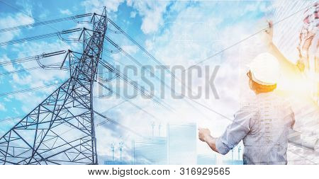 Electrical engineer and innovation technology concept. Electrician hold the blueprint with high voltage pole background. stock photo