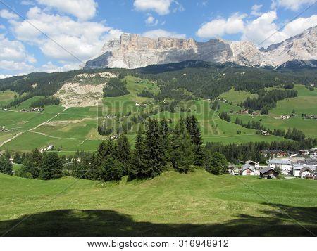 Alpine landscape with La Villa village, green pastures and firs against italian Dolomites at summer . La Villa, Bolzano, Alto Adige, South Tyrol, Italy stock photo