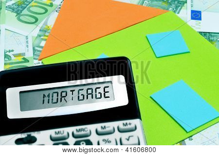 word mortgage written in the display of a calculator, and a depiction of a house on a pile of euro bills stock photo