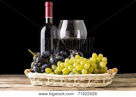Winery still-life. varieties of grapes with wineglass and bottle of white wine on black background