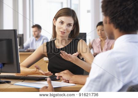 Two Business People Having Meeting In Busy Office