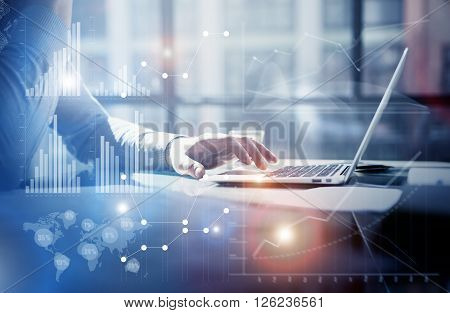 Business concept photo.Businessman working investment project modern office.Touching pad contemporary laptop. Worldwide connection technology, stock exchanges graphics interface.