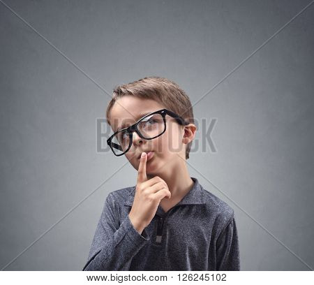 Thinking child deep in thought concept for confusion, brainstorming, indecision, uncertainty and cho