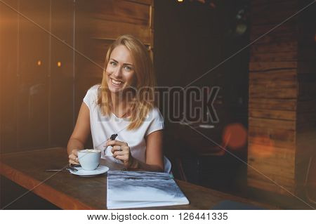 Attractive happy hipster girl with good mood posing while sitting alone in modern coffee shop interior cheerful Caucasian woman with beautiful smile enjoying her recreation time in cozy cafe bar