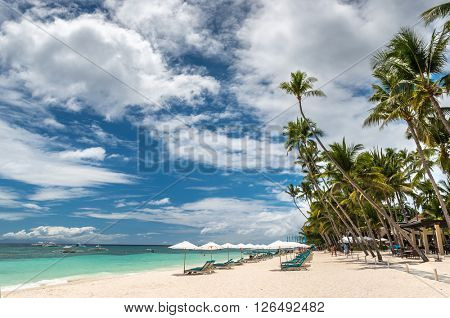 Tropical beach background from Alona Beach at Panglao Bohol island with beach chairs on the white sa