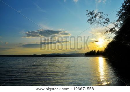 Summer silhouette landscape - sunset over the Ural mountains and Irtyash lake in Southern Urals Russia stock photo