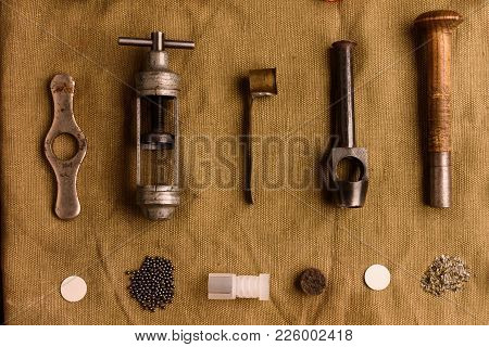 Many accessories for reloading hunting cartridges lie on the old cloth. Taping, die cutting, measuring for gunpowder, twisting for cartridges. stock photo