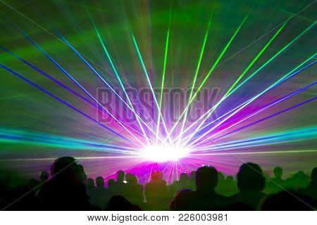 Laser show rays. Very colorful show with a crowd silhouette and great laser rays on pyrotechnic festival. stock photo