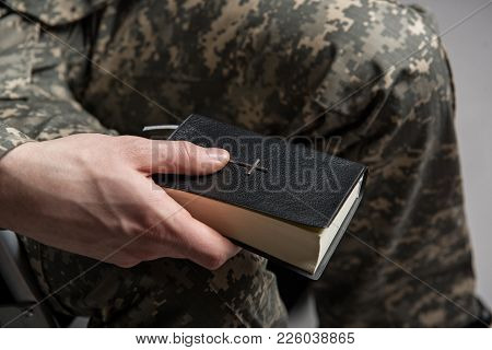 Close up of male hand holding the Bible. Disabled male veteran sitting and praying. He is wearing military uniform. Focus on the Bible stock photo