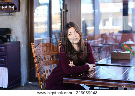Manicurist replenish mobile account using smartphone and bank card, Asian girl sitting at wooden table near big window in coffee house with antique interior. Young woman with long fair hair and red manicure entering data. Concept of innovative technologie stock photo