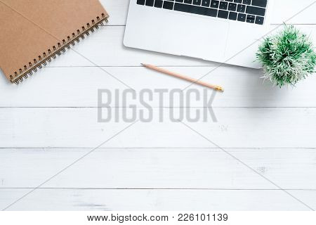 Minimal work space - Creative flat lay photo of workspace desk. Top view office desk with laptop, mock up notebooks and plant on white wooden background. Top view with copy space, flat lay photography stock photo