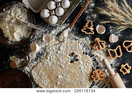 Dough for ginger biscuits rolled up on a table and cut using molds. Top view with copy space, mockup for menu, recipe or culinary classes. Baking background. Still life. Flat lay stock photo