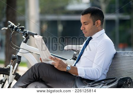 Serious busy man searching job in newspaper while sitting on bench in park. Concentrated modern male analyst with bicycle reading article in morning newspaper. Business lifestyle concept stock photo