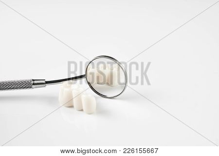 Removed dental teeth and dentistry instruments for tooth removal, dental mirror at the dentist office, isolated on white background with copy space, close-up. Oral dental hygiene concept stock photo