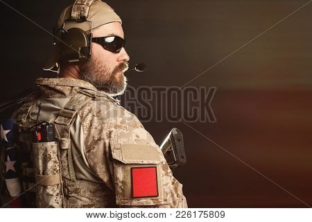 Brutal man in the military desert uniform and body armor is pathetic and looks away at the black background in the Studio. The bearded player in the airsoft safety goggles is holding his rifle. stock photo