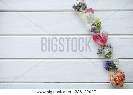petals and cubes of ice of heart with flowers inside on a white wooden background stock photo