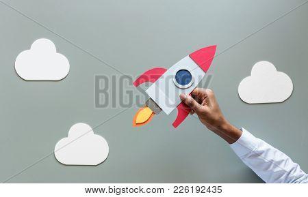 Hand holding rocketship startup business