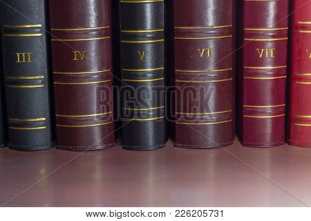 Fragment of several black, cerise and red book spines of the old tomes of the collected works in leather-bound on the shelf stock photo