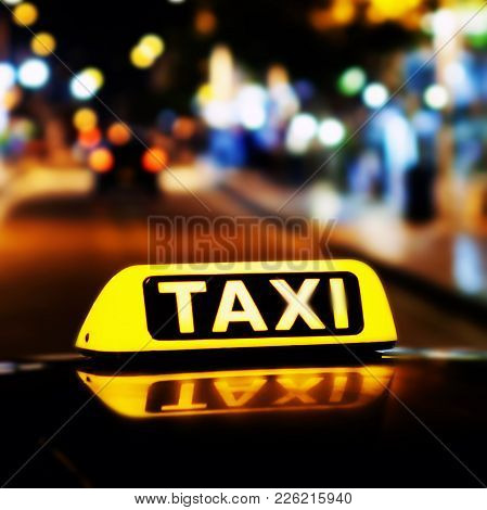 Taxi sign on the roof of a taxi at night close-up stock photo