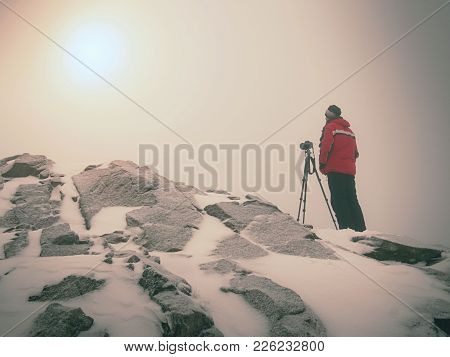 Man in warm clothes enjoy photographying in wild winter nature. Nature photographer looking into viewfinder of  big camera on tripod. Snowy summit rock. Listen to muse. stock photo